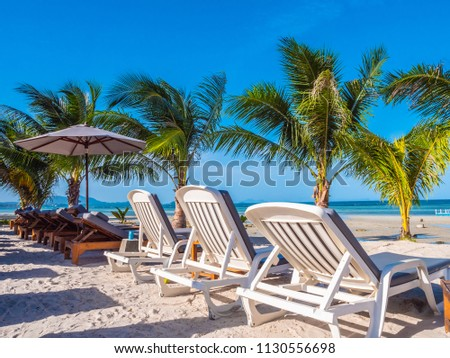 Umbrella and chair on the beach and sea ocean with blue sky around coconut palm tree for travel and vacation #1130556698