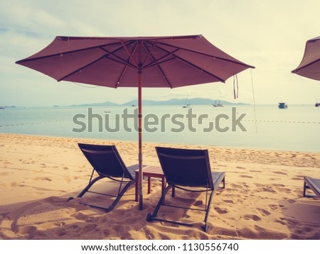 Umbrella and chair on the tropical beach sea and ocean at sunrise time for travel and vacation #1130556740