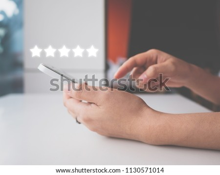 Woman hand using smart phone with icon five star symbol to increase rating of company concept Royalty-Free Stock Photo #1130571014