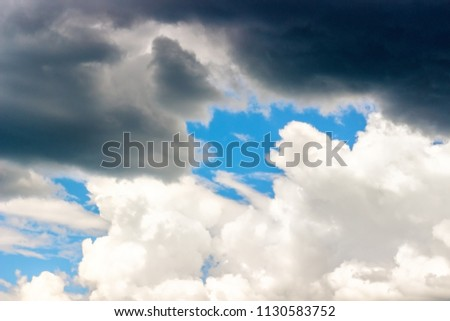 Dark Storm and White Cumulus clouds in the blue sky, background, texture Concept - the fight between good and evil Royalty-Free Stock Photo #1130583752