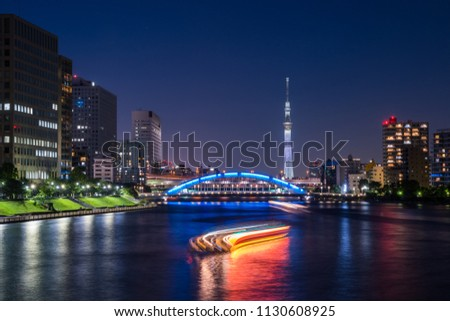 """CHUO, TOKYO / JAPAN - JULY 1 2018 : Night view of Sumida River and """"Eitai Bridge"""". Many sightseeing ships pass under the bridge. In the distance you can see the lighted """"TOKYO SKYTREE"""". #1130608925"""