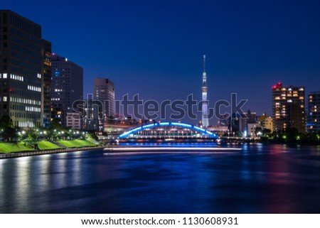 "CHUO, TOKYO / JAPAN - JULY 1 2018 : Night view of Sumida River and ""Eitai Bridge"". Many sightseeing ships pass under the bridge. In the distance you can see the lighted ""TOKYO SKYTREE"". #1130608931"