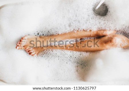 Woman legs in bath foam. Top view. Enjoying and relaxation in spa hotel #1130625797