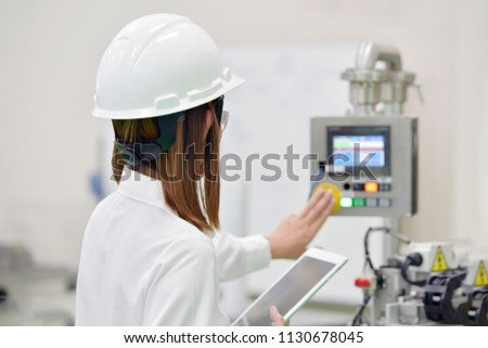 Asian girl engineer wearing a safety helmet and a white safety helmet.while working with a laptop for Machine Controller in the factory . #1130678045