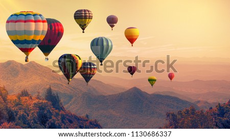 Hot air balloon above high mountain at sunset, filtered background Royalty-Free Stock Photo #1130686337