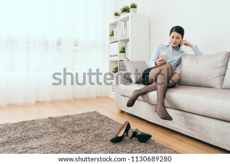 beautiful business lady sitting on the sofa using smartphone take rest in the living room at home #1130689280