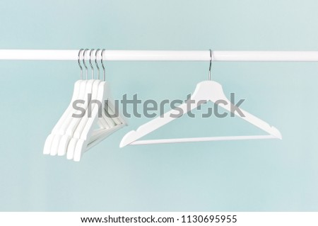Many wooden white hangers on a rod, isolated on blue turquoise wall background. Store concept, sale, design, empty hanger. Place for your text #1130695955