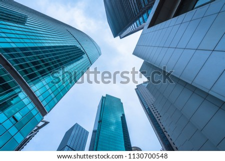 Bottom view of modern skyscrapers in business district against blue sky #1130700548