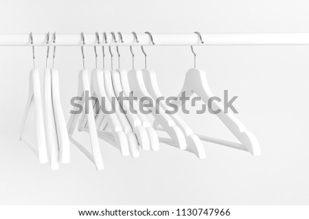 Many wooden white hangers on a rod, isolated on white wall background. Store concept, sale, design, empty hanger. Place for text. #1130747966