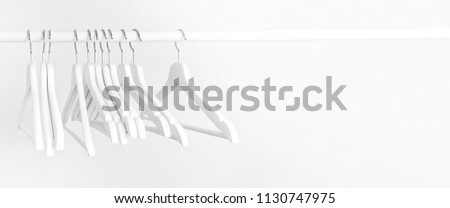 Many wooden white hangers on a rod, isolated on white wall background. Store concept, sale, design, empty hanger. Place for text. #1130747975