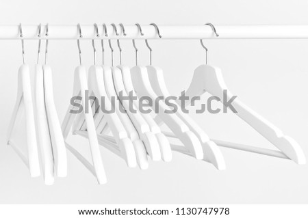 Many wooden white hangers on a rod, isolated on white wall background. Store concept, sale, design, empty hanger. Place for text. #1130747978