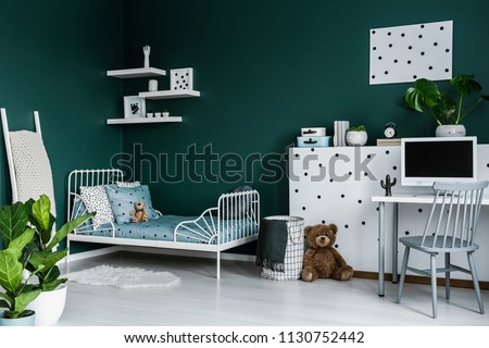 Plants near bed in green child's bedroom interior with grey chair at desk near plush toy #1130752442