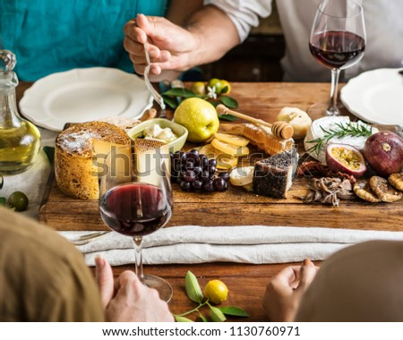 People eating a platter of cheese with seasonal fruits and wine #1130760971