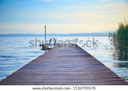 Long wooden pier at Lake Garda in Italy at sunset / slightley blurred picture with nice bokeh