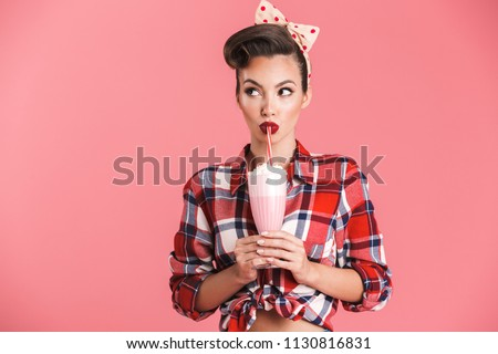 Portrait of a cheerful brunette pin-up girl in plaid shirt holding milk shake and looking away over pink background #1130816831
