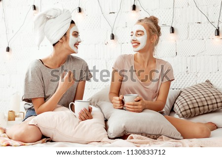 Portrait of pretty joyful friends doing beauty treatments at home. Cheerful young women relaxing in cozy bedroom and drinking coffee. Skincare concept #1130833712