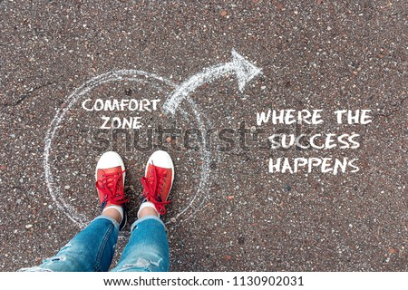 Exit from the comfort zone concept. Feet  in red sneakers standing inside circle comfort zone and outward arrow chalky on the asphalt. #1130902031