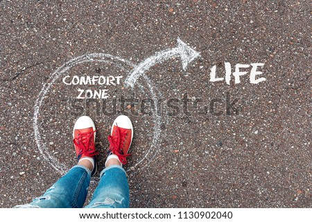 Exit from the comfort zone concept. Feet  in red sneakers standing inside circle comfort zone and outward arrow chalky on the asphalt. #1130902040