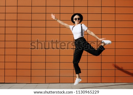 Bright fashion hipster young woman with stylish sunglasses and black hat jump near wall. Freedom concept. #1130965229