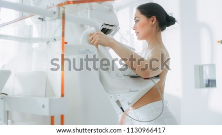 In the Hospital, Portrait Shot of Topless Female Patient Undergoing Mammogram Screening Procedure. Healthy Young Female Does Cancer Preventive Mammography Scan. Modern Hospital with High Tech Machines #1130966417
