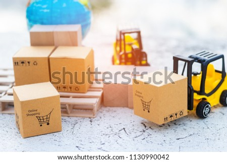 Close up mini forklift truck load cardboard box with shopping cart symbol and globe near by. Logistics and transportation management ideas and Industry business commercial concept. #1130990042
