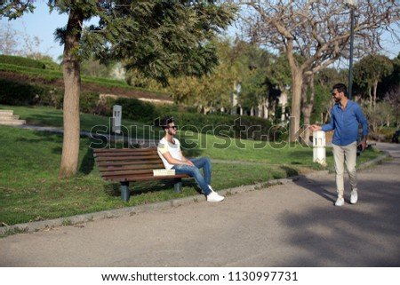 two friends in park , one sitting on bench and other one greeting him #1130997731