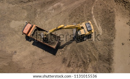 Aerial photo of excavator pours sand into the truck. On the construction site top view. Shooting from the drone.