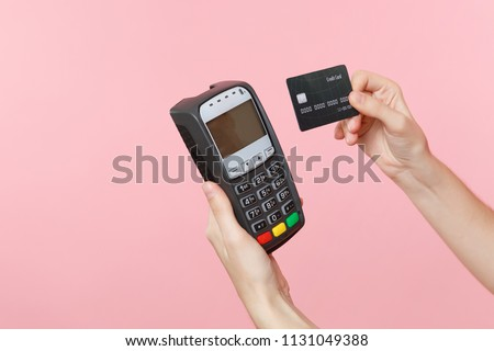 Close up cropped photo of female holding in hands wireless modern bank payment terminal to process and acquire credit card payments, black card isolated on pink background. Copy space for advertising