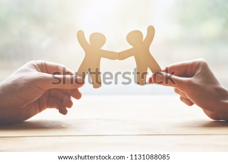 couple holding in hands wooden toy men as symbol of love and friendship Royalty-Free Stock Photo #1131088085