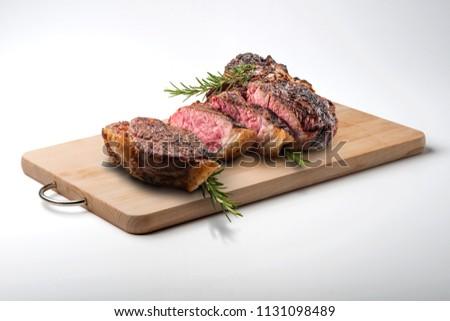 Fiorentina T-bone steak cut on rectangular wooden chopping board isolated on white background #1131098489