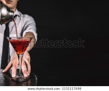 Expert barman making cocktail at nightclub.  Bartender preparing red cocktail at cocktail glass at the bar. Preparing of cosmopolitan cocktail. Red alcoholic drink in glasses on bar.  #1131117698