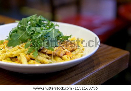 Penne pasta in creamy sauce with chicken top with salad on a wooden table #1131163736