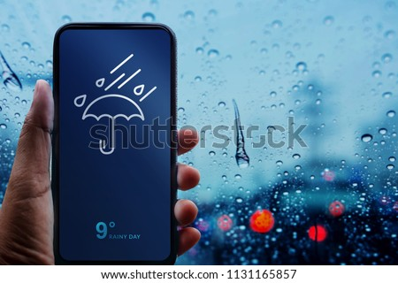 Rainy Day Concept. Hand Holding Smartphone with Weather Information show on Screen. Blurred Traffic Jam and Rain Drops on Glass Window as background  Royalty-Free Stock Photo #1131165857
