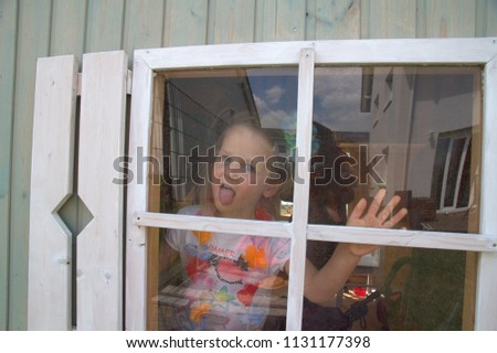 A little girl looks through a window in a wooden house #1131177398