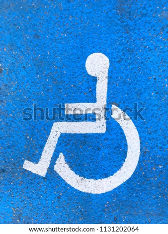 Painted parking space for handicapped. Wheelchair parking lot symbol. Empty space for text. #1131202064