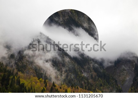 Geometric effect is a reflection of the landscape. Bright yellow trees in autumn. The slopes of the mountains are covered with a mixed forest. The tops are hiding in the clouds #1131205670