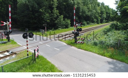 Aerial picture level crossing and railway tracks the crossing is an intersection where a railway line crosses a road or path at same level beautiful single track in forest landscape