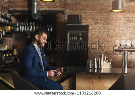 Smiling businessman using smartphone at bar, networking and having nice time after hard workday, copy space #1131216200