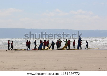 Surfers on westward Ho beach Royalty-Free Stock Photo #1131229772