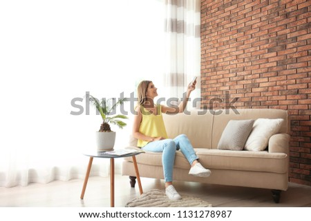 Woman with air conditioner remote at home #1131278987