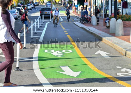 Two-way protected bike lanes with pavement markers, striped median, buffer zone and flexible delineators in city street Royalty-Free Stock Photo #1131350144