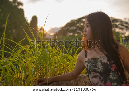 Women with the sun shines through the grass in the morning. #1131380756