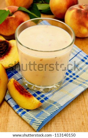 Milk shake in a glass beaker with peaches on a napkin on the background of wooden boards #113140150