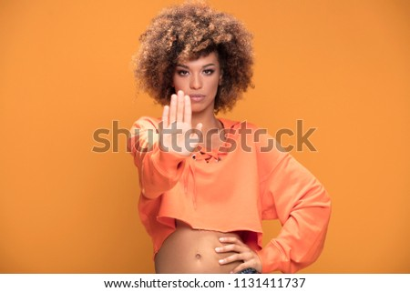 Young african american woman making stop sign with hand, saying no, looking at camera. Yellow studio background.