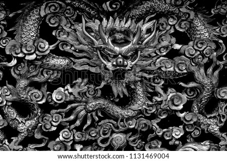 Close up view of wooden carving of a traditional ancient Chinese dragon in monochrome with intricate craftsmanship and detail as vintage background  #1131469004