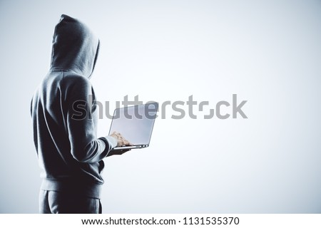 side view on hacker in grey hoody with laptop at white background. #1131535370
