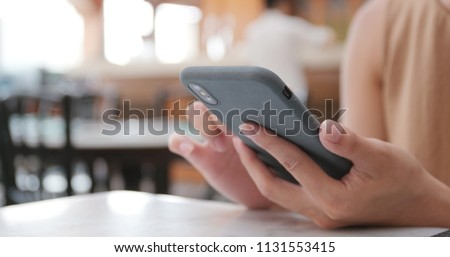 Woman use of mobile phone in restaurant #1131553415