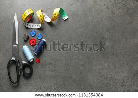 Set of tailoring accessories on grey background, top view #1131554384