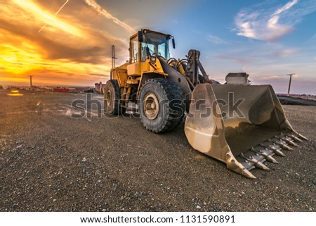 Excavator at the end of a working day at a construction site in a beautiful evening #1131590891