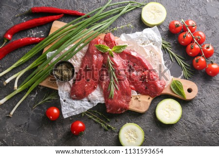 Fresh raw meat with spices, herbs and  vegetables on grey background #1131593654